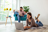 Couple reading newspapers and using laptop computer