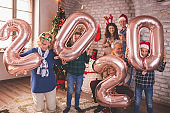 Family holding balloons shaped as numbers 2020