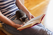 Woman cuddling kitten and reading a book