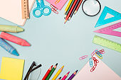 School supplies on blue background. Education concept, top view copy space.