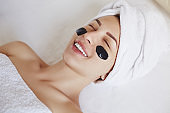Young beautiful spa woman with towel on her head applying black mask cleaning pores. Skin care, spa salon and beauty Treatments