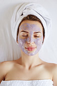 Young beautiful spa woman with towel on her head applying facial clay mask cleaning pores. Skin care, spa salon and beauty Treatments