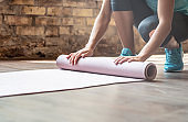 Woman rolling yoga pilates rubber mat on gym studio floor, female fit sporty lady preparing for sport workout exercise fitness class close up view, training routine equipment background concept