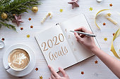 Woman writing in notebook goals plans wish list for new year 2020, flat lay