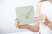 Close-up photo of female hands holding invitation envelope with a wax seal, a gift certificate, a postcard, wedding invitation card.