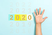 2020 new year resolution change sign text concept with hand palm raised on blue background