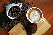 White coffee mugs and coffee beans Poured on a wooden table, beautifully arranged, decorated with coffee leaves. Is a mixture of raw materials for making coffee