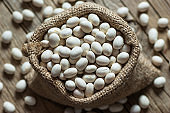 White dried haricot kidney beans on wooden table , heap of legume bean concept. Legumes background