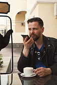 Trendy man on summer terrace cafe with smartphone
