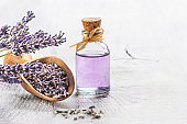 Glass bottle of Lavender essential oil with fresh lavender flowers and dried lavender seeds on white wooden rustic table, aromatherapy spa massage concept