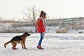 Teenager girl and German shepherd. Winter