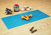 Pilates mats, balls, dumbells and other fitness equipment laid on the floor