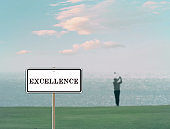 Excellence sign with a golfer on background