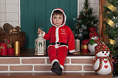 Smiling boy dressed as Santa Claus standing in front of Christmas tree decorated for Christmas.