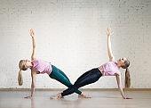 Caucasian girls practice side plank in fitness studio, selective focus.