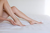 Female beautiful legs on white bedding. Caucasian woman touches her skin, close up. Ivory pedicure and manicure
