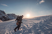 Man photographer climbing on snowy mountain with blue sky at sunset