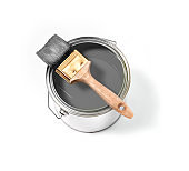 Grey paint tin can with brush on top on a white background