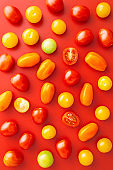 Cherry tomato pattern on a red background viewed from above. Red, orange, yellow and green tomatoes isolated on a solid background. Top view