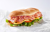 Salami sandwich made from bun, sliced ham and fresh letttuce, tomato and cheese. Healthy breakfast. Copy space