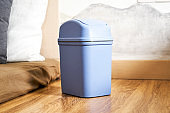 Blue small trash can placed on the bedside
