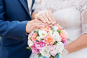 Hands of groom and bride with wedding rings and flowers bouquet. concept of love and marriage