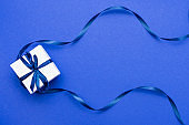 gift box wrapped with classic blue ribbon on blue background. Top view. copy space