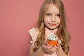 small girl in hand holds a sweet cupcake cake candy