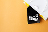 Black Friday shopping bag on yellow background. Copy space