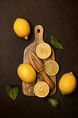 Fresh lemons with a wooden juicer on a cutting board on a dark background.