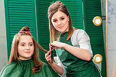 Hairdresser makes hairstyle for beautiful woman.
