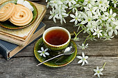 A cup of tea vintage on the background of a bouquet with white flowers, old books, cookies and an old wooden background