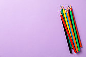 Multicolor pencils on violet background, space for text