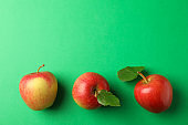 Flat lay with red apples on green background, space for text