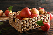 Basket with apples on wooden background, copy space