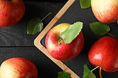 Apples and cutting board on wooden background, top view