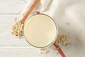 Glass of oat milk, spoon with oatmeal seeds and napkin on white, wooden background, top view. Closeup