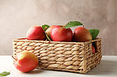Basket with apples on white wooden background, copy space