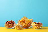 Beer snacks, potato chips, crackers in a bowl on yellow background against blue background, space for text