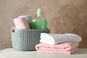 Basket with clean towels and laundry liquid on wooden background, space for text