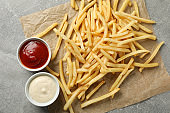 Tasty french fries, sauces on gray background, space for text. Top view