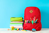 School supplies on wooden table against color background, space for text
