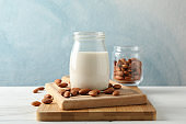 Glass of almond milk, almond seeds on white table again blue background, space for text