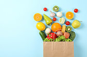 Flat lay with paper bag, vegetables and fruits on blue background, copy space