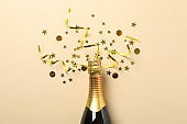 Champagne bottle and glitter on beige background, space for text