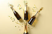 Champagne bottles and glitter on beige background. Holiday concept