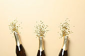 Champagne bottles and glitter on beige background, space for text