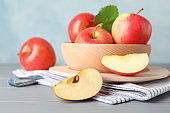 Bowl with apples on wooden background, close and space for text