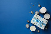 Gift box, Christmas baubles and candles on blue background, space for text