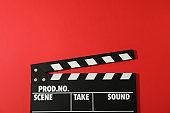 Black clapperboard on red background, space for text